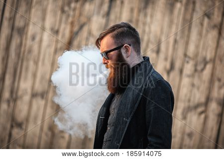 Vape Man. Outdoor Portrait Of A Young Brutal White Guy With Large Beard And In Sunglasses Letting Pu