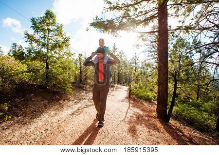 A man with his baby boy are hiking in Bryce canyon National Park Utah USA