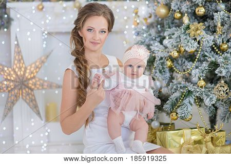 Mom mother with a little sweet and beautiful daughter spends time plays, coos, sitting next to the Christmas tree.