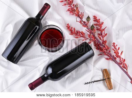Wine glass in the center of two bottles laying on their sides on white fabric surface with corkscrew and flowers. Horizontal orientation.