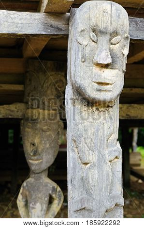 The culture and beliefs of the island Borneo. Traditional Dayak tribal culture. Totem in front of Dayak house - long house. Kalimantan Indonesia