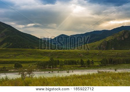 The ray of the sun makes its way through the clouds. Mountains and hills. The Katun River.
