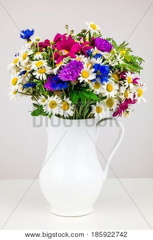 Wildflowers in white ceramic jug. Wild flower bouquet on white table. Bunch of wild herbs and flowers in a white jug. Wild flowers in a vase.