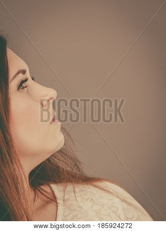 Woman having serious face expression profile side shot with copyspace on grey background.