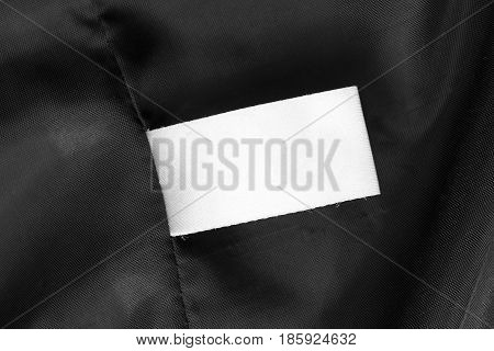 Blank white clothes label on black silk closeup as a background