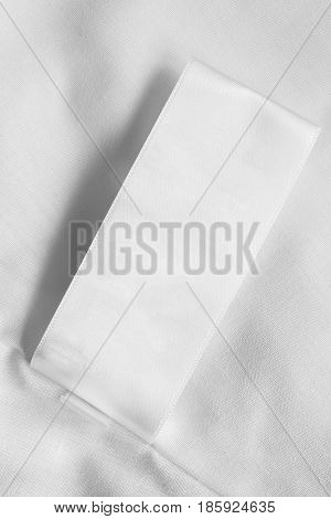 White blank clothes label on white cloth as a background