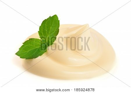 Mayonnaise swirl with a mint leaf isolated on a white background close-up.