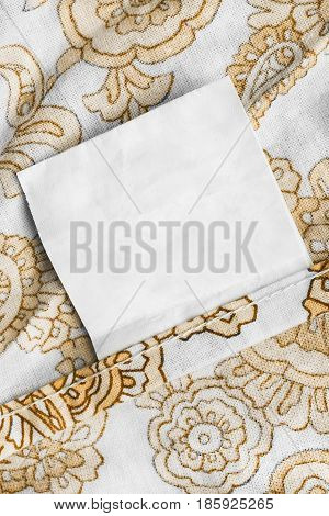 Blank clothes label on white and yellow cotton closeup as a background