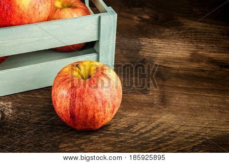 A closeup of a red and yellow apple in front of a teal crate, on a rustic wooden background texture, with a place for text, selective focus