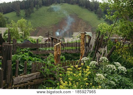 An interesting foreshortening of rural Russian life. Old wooden buildings plots with houses and smoke from the chimney.