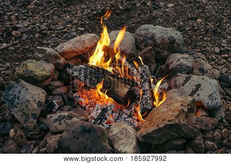 Evening small fire made of birch logs ennobled with stones. Warm hearth.