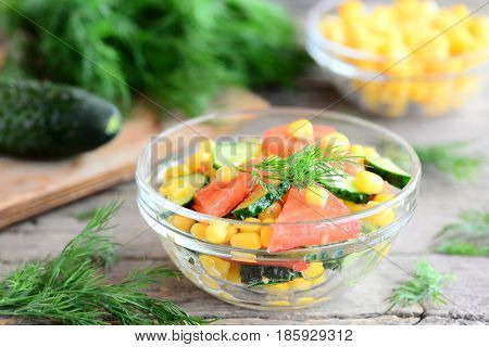 Vegetable salad. Summer salad with fresh cucumbers, tomatoes, corn, dill and olive oil and lemon dressing. Delicious and simple salad or side dish recipe. Vegetables and dill on a vintage wooden table
