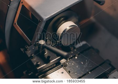 CNC lathe or CNC Turning machine threading the metal shaft with high rotation speed in dark settings and shallow depth of field