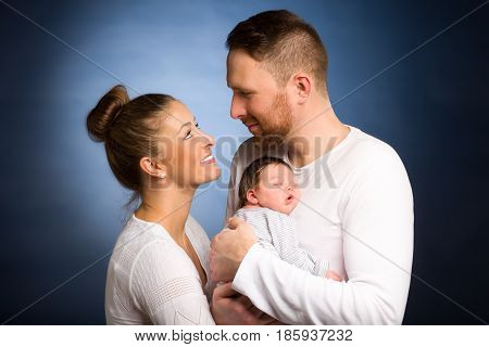 Portrait of young happy couple embracing to their newborn over a dark background. Family and baby care concept.