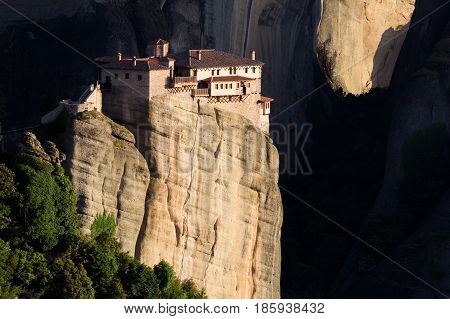 Beautiful scenic view of the Orthodox Monastery of Rousanou (St. Barbara) on a monolithic pillar with a dark shadow background in Meteora Pindos Mountains Greece
