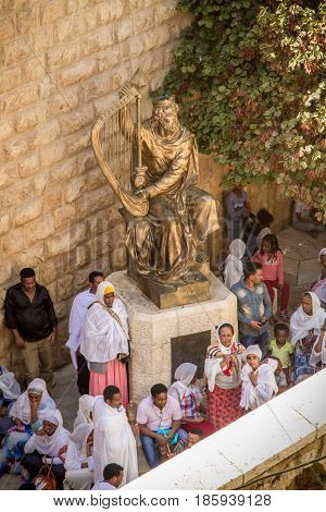JERUSALEM, ISRAEL - OCTOBER 3: The statue of King David playing the harp, people near entrance to his tomb on Mount Zion in Jerusalem, Israel on October 3, 2016