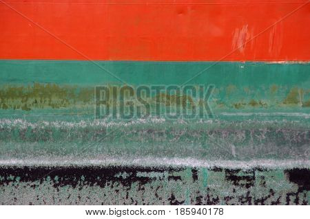Orange and green paint on rusty ship hull