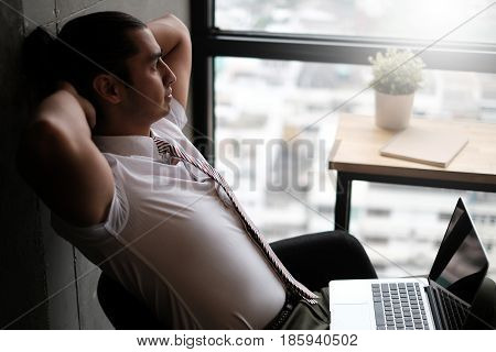 Young office worker is relaxing in his chair and enjoying the view from office window