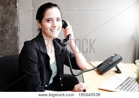 Smiling young businesswoman talking on phone in office