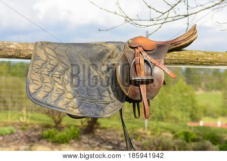 Leather cowboy saddle hanging on the railing. Removable saddle for horse in fresh air. Saddle hanging on a fence with a forest background.