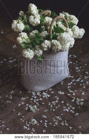 top view closeup of wicker bag with knitted handles full of white snowball flowers on wooden background with petals around in natural light