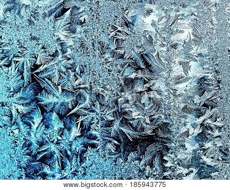 beautiful frosty pattern with swirls and feathers on cold glass