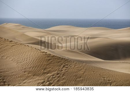 Maspalomas dunes in Gran Canaria with the ocean in the background. The sand of the dunes is taken by clouds from Sahara desert