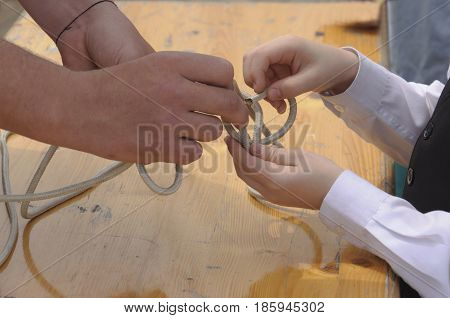 The captain teaches boy to tie the knot on the deck of the frigate in Russia