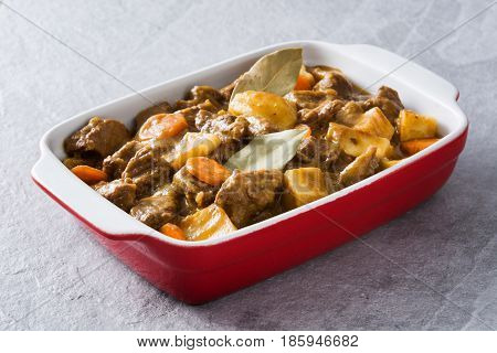 Beef meat stewed with potatoes, carrots and spices in ceramic pot on gray stone