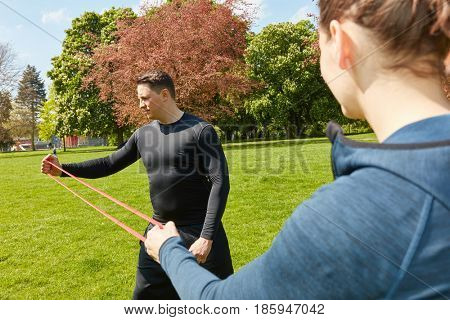 Man fitness training with rubber band in the park