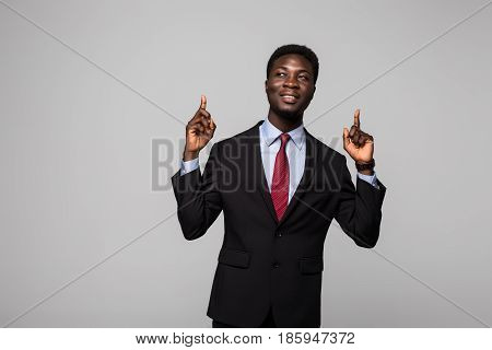 Handsome Young African Man In Suit Pointing Up And Smiling While Standing Against Grey Background