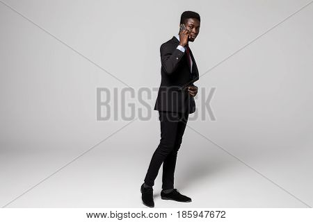 Full Height Confident Young African Man Talking On Mobile Phone While Standing Against Grey Backgrou