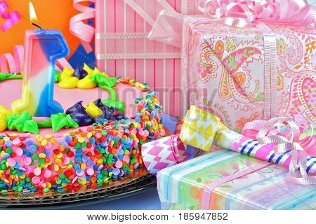 Gifts, noise makers, and balloons surround a pink and femininel birthday cake with a lit number one candle.