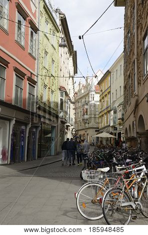 GRAZ, AUSTRIA - MARCH 19, 2017: Bicycles parked and people strolling by a side street of Herrengasse in the old city of Graz the capital of federal state of Styria Austria.