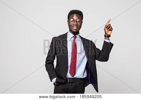 Businessman Pointing At Something On Grey Background