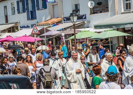 Saintes-Maries-de-la-Mer, France - May 25, 2015. Religious holiday in honor of the Holy Maries in Provence. The concept of ethnographic tourism. Participants of a procession bear banners