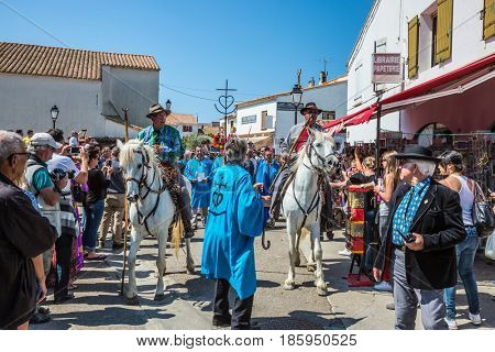 Saintes-Maries-de-la-Mer, Provence, France - May 25, 2015. Religious feast in honor of the Holy Maries. Guards on white horses and participants in a procession. The concept of ethnographic tourism