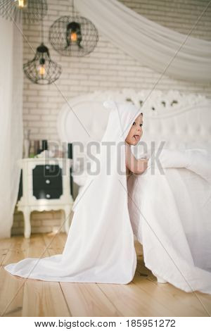 Newborn Baby Five Month Old Baby In The Bedroom Next To A Large White Bed On The Wooden Floor Wrappe