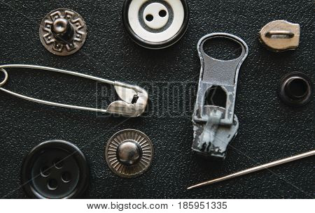 pin buttons of various sizes and colors sliders for zippers needle buttons textural elements on a dark background