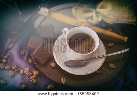 Cup of fresh hot coffee in the morning sunshine, coffee beans, turk, dark chocolate on dark wooden background. Low key image in vintage style. Concept of the hormone of happiness and good mood