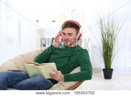 Concept of audiobook. Handsome young man with headphones and book sitting in armchair at home