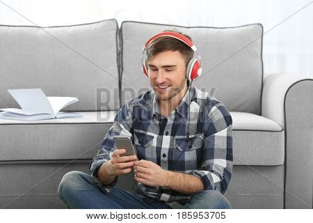 Concept of audiobook. Handsome young man with headphones and phone sitting on floor at home