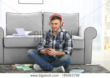 Concept of audiobook. Handsome young man with headphones and phone sitting on carpet at home