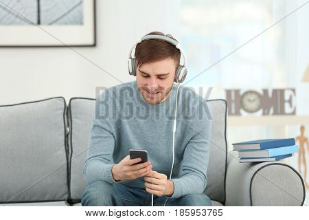 Concept of audiobook. Handsome young man with headphones and phone sitting on sofa at home