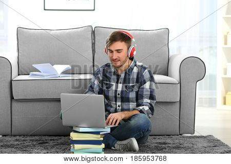 Concept of audiobook. Handsome young man with headphones and laptop sitting on carpet at home