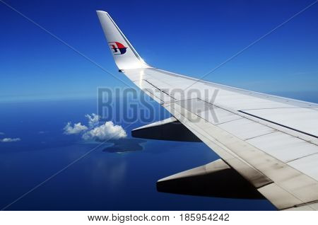 KOTA KINABALU, MALAYSIA - APRIL 05, 2017: Malaysia Airlines MAB logo airplane in flight with plane's wing logo..