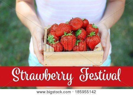 Text STRAWBERRY FESTIVAL and woman with wooden crate of fresh berries on background