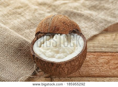 Fresh coconut oil in half of nut on wooden table