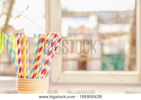 Plastic cups with straws on blurred background