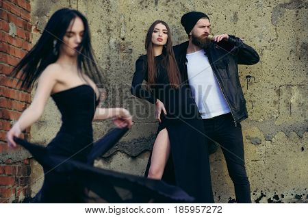 people outdoor dancing woman in black dress girl and bearded man drink from bottle near wall couple in love